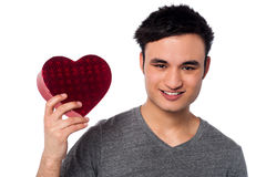 Young man holding heart shaped box Stock Photos