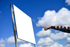 Young man holding his arm out presenting a blank board outside Stock Photography