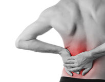 Young man holding his back in pain, isolated