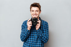 Young man holding his camera in hands. Young handsome man holding his camera in hands Royalty Free Stock Photography