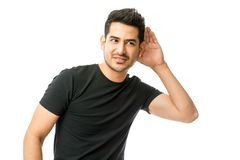 Young Man Holding His Hand Near Ear And Listening Carefully. Over white background stock photography