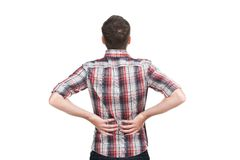 Young man holding his hand to his aching back. Royalty Free Stock Photo
