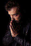 Young man holding his hands together praying. Royalty Free Stock Image