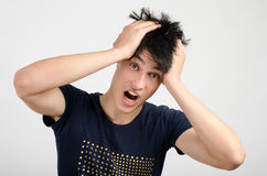 Young man holding his head frowning with worry screaming. Man pulling his hear for worry, sadness, desperation.Man with different facial expressions Royalty Free Stock Image