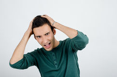 Young man holding his head frowning with worry screaming. Man pulling his hear for worry, sadness, desperation.Man with different facial expressions Stock Photography