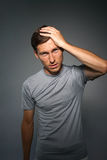 Young man holding his head. Gesture of annoyance or headache. Stock Photo