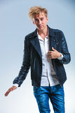 Young man holding his leather jacket while smiling at the camera Royalty Free Stock Images