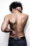 Young man with lower back and neck pain. Young man holding his lower back and neck in agony Stock Photos