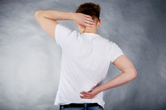 Young man holding his neck in pain. Royalty Free Stock Photos