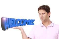 Young man holding with his right hand the write `WELCOME` in blue 3D letters Stock Image
