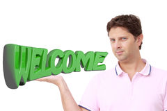 Young man holding with his right hand the write `WELCOME` in green 3D letters Royalty Free Stock Photos