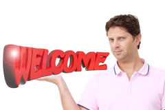 Young man holding with his right hand the write `WELCOME` in red 3D letters Stock Image