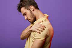 Young man holding his shoulder and looking down stock photos