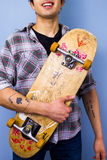Young man holding his skateboard. Smiling young multiracial man with a vintage skateboard Stock Photo
