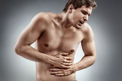 Young man holding his stomach in pain. Abdominal pain. Young man holding his stomach in pain. Medical concept Stock Image
