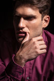 Young man holding his thumb to his lip. Stock Images