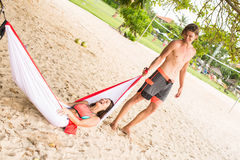 Young man holding his wife in a hammock Stock Photography