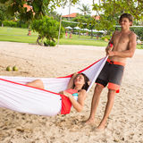 Young man holding his wife in a hammock Royalty Free Stock Photo