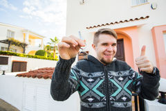 Young man holding house keys on house shaped keychain in front of a new home. Young man holding house keys on house shaped keychain in front of a new home Royalty Free Stock Image