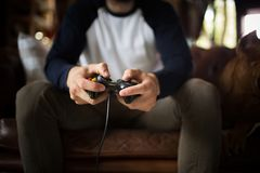 A young man holding joystick, playing video game. Man sitting on sofa, playing video games on console stock photos