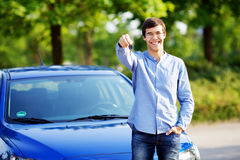 Young man holding key of his new car Stock Photo