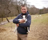 Young man holding a kid goat. stock photography