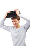 Young man holding a laptop above head Royalty Free Stock Images