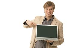 Young man holding laptop with blank screen Stock Images