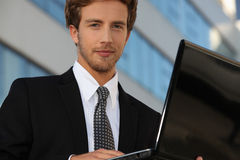 Young man holding laptop Stock Images