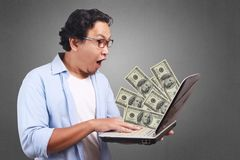 Young Man Holding Laptop, Money Sign. Young Asian man holding laptop and winning plenty of money in social media. Close up body portrait royalty free stock photography