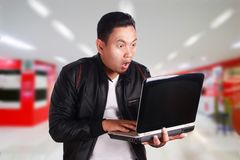 Young Man Holding Laptop. Portrait of young attractive Asian man wearing black leather jacket holding laptop, shocked expression Royalty Free Stock Images