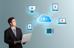 Young man holding a laptop and presenting cloud computing networ Royalty Free Stock Image