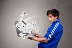 Young man holding a laptop and reading the explosive news Royalty Free Stock Images