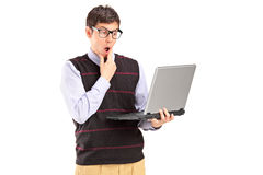 Young man holding a laptop and thinking Royalty Free Stock Image
