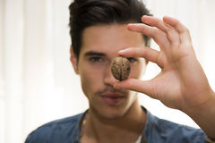 Young man holding a large delicious nut Royalty Free Stock Photography