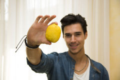 Young man holding a large delicious ripe lemon Stock Image