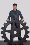 Young man holding a large gear Royalty Free Stock Photo