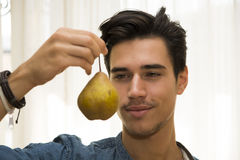 Young man holding a large ripe yellow pear Stock Images