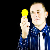 Young man holding light bulb in hand Royalty Free Stock Images