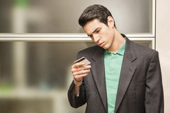 Young man holding and looking at credit card Royalty Free Stock Photos