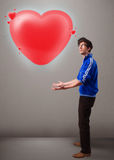 Young man holding lovely 3d red heart Stock Image