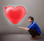 Young man holding lovely 3d red heart Royalty Free Stock Image