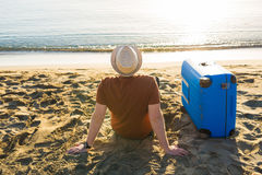 Young man holding luggage at the sea. Travel, summertime, holidays and people concept. Stock Photography