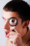 Young man holding a magnifier on his eye Stock Photography