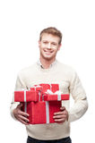 Young man holding many red christmas gifts. Young casual caucasian man holding many red christmas gifts with nice toothy smile Royalty Free Stock Photo
