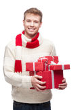Young man holding many red christmas gifts. Young casual caucasian man holding many red christmas gifts with nice toothy smile Royalty Free Stock Photography