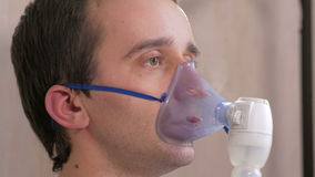 Young man holding a mask from an inhaler at home. Treats inflammation of the airways via nebulizer. Preventing asthma stock video