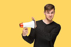 The young man holding a megaphone. On on yellow studio background Royalty Free Stock Image