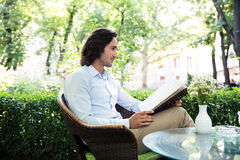 Young man holding menu in cafe. Young man holding menu in outdoors cafe Royalty Free Stock Photography