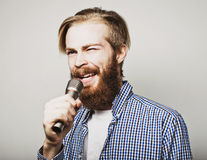 Young man holding a microphone and singing Royalty Free Stock Photo